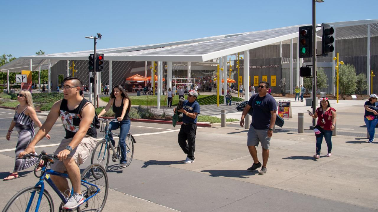Students crossing the street on foot and on bikes in front of the museum.