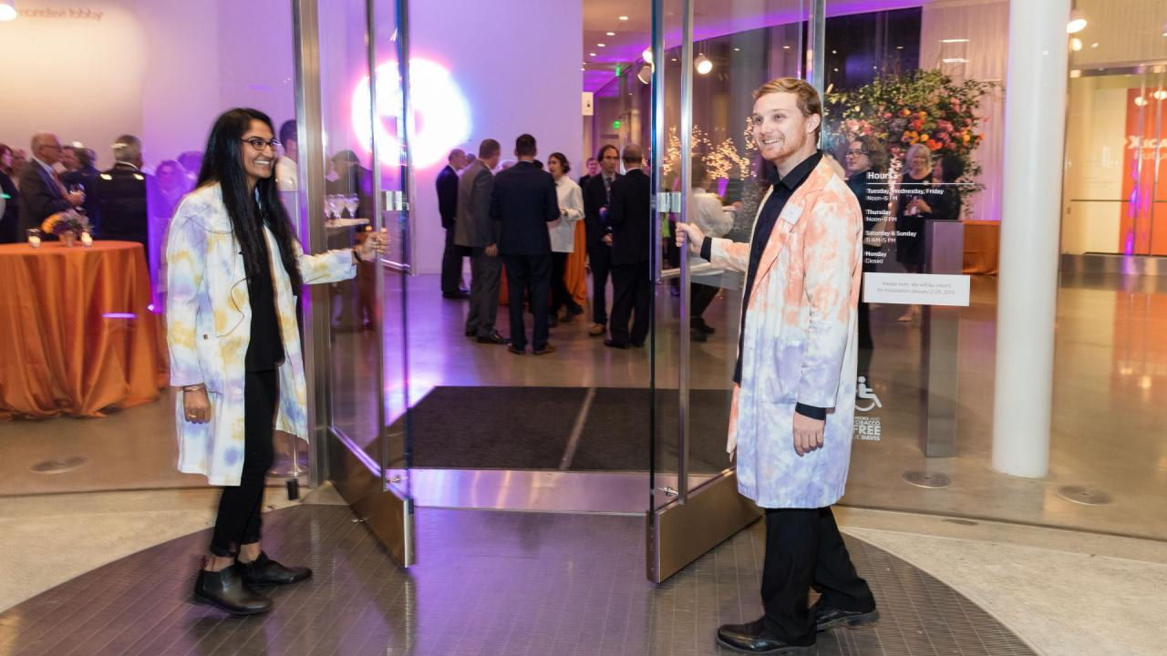 Two students opening the doors of the museum on gala night.