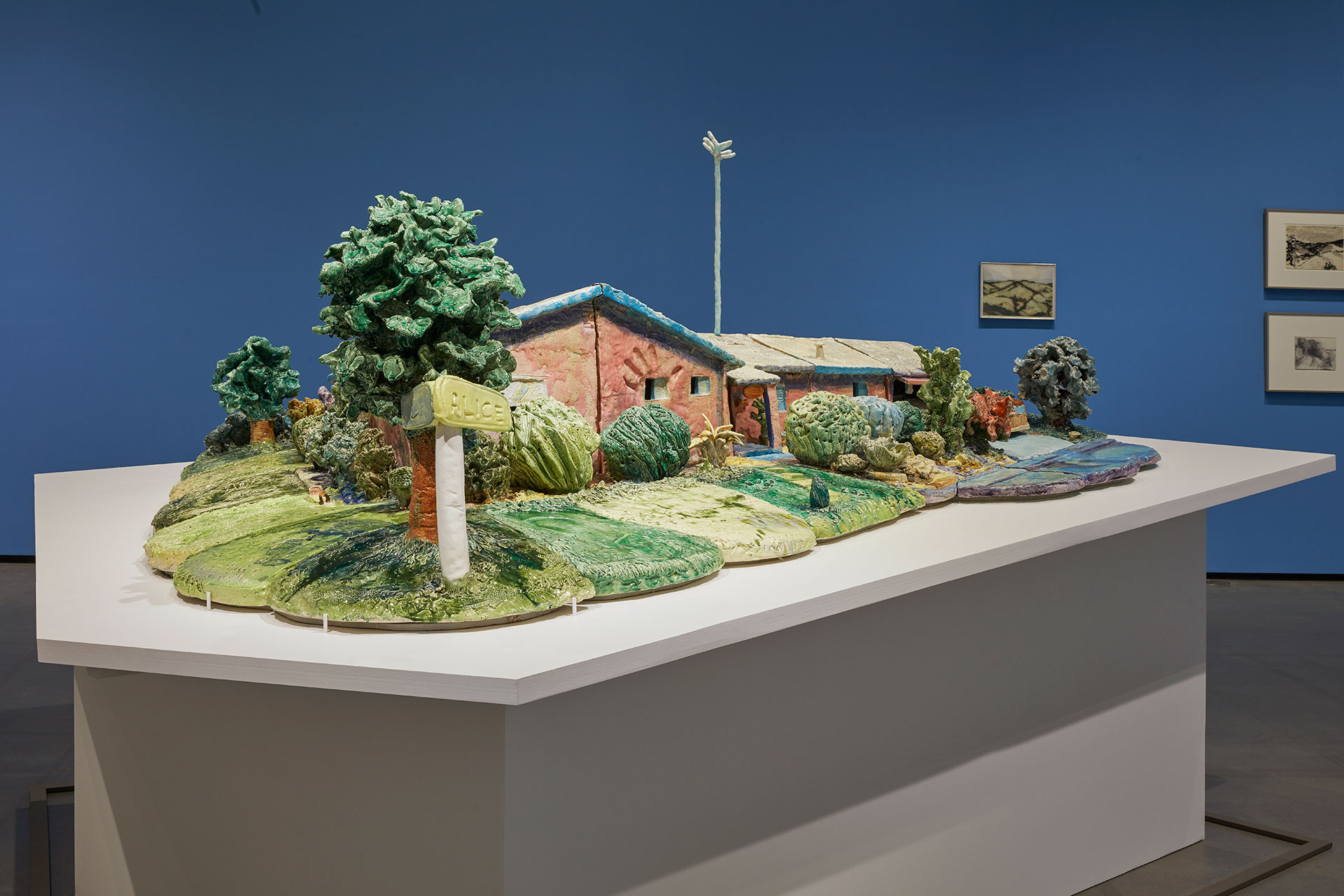 Ceramic sculpture of a house with yard and tree.