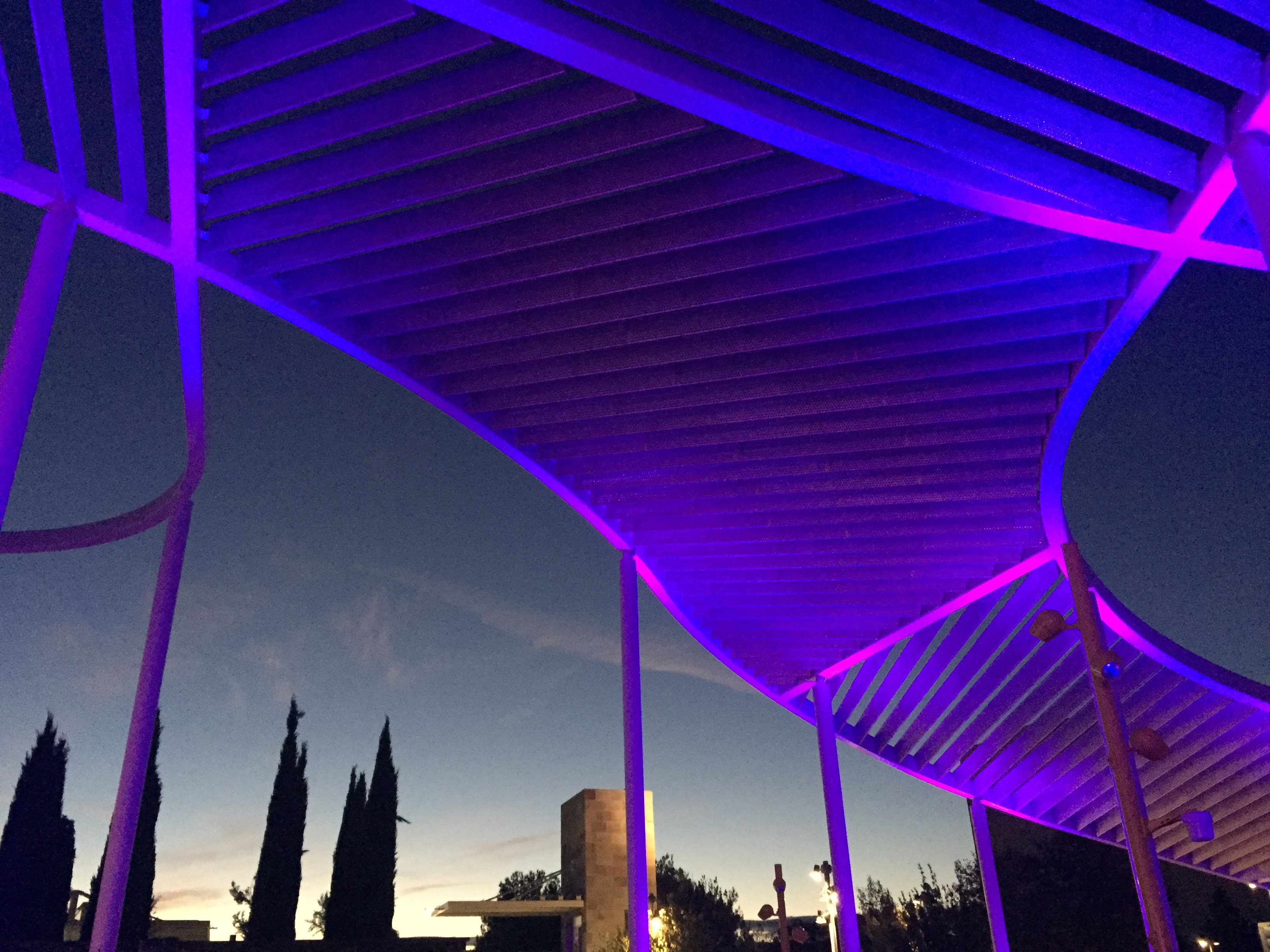 Photo of the museum canopy lit with purple light at night.