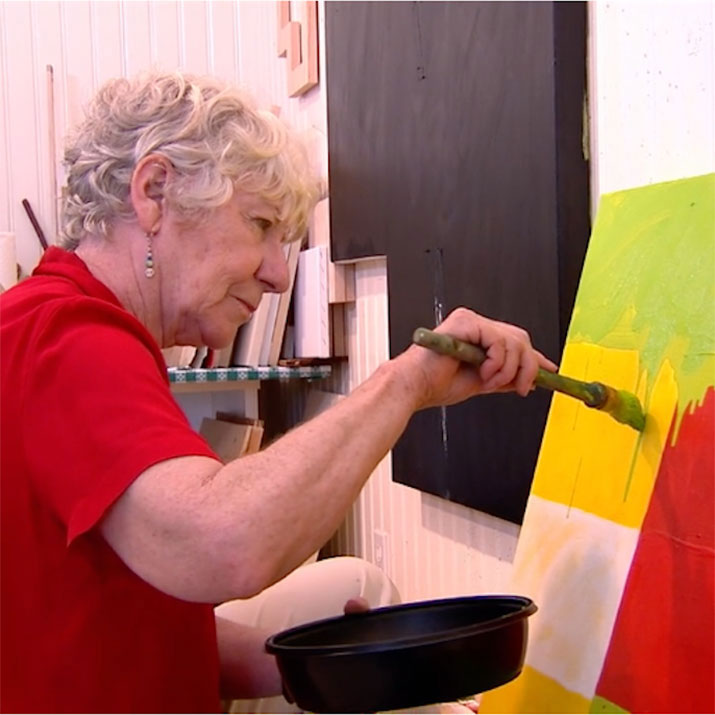 Woman painting a canvas in art studio.