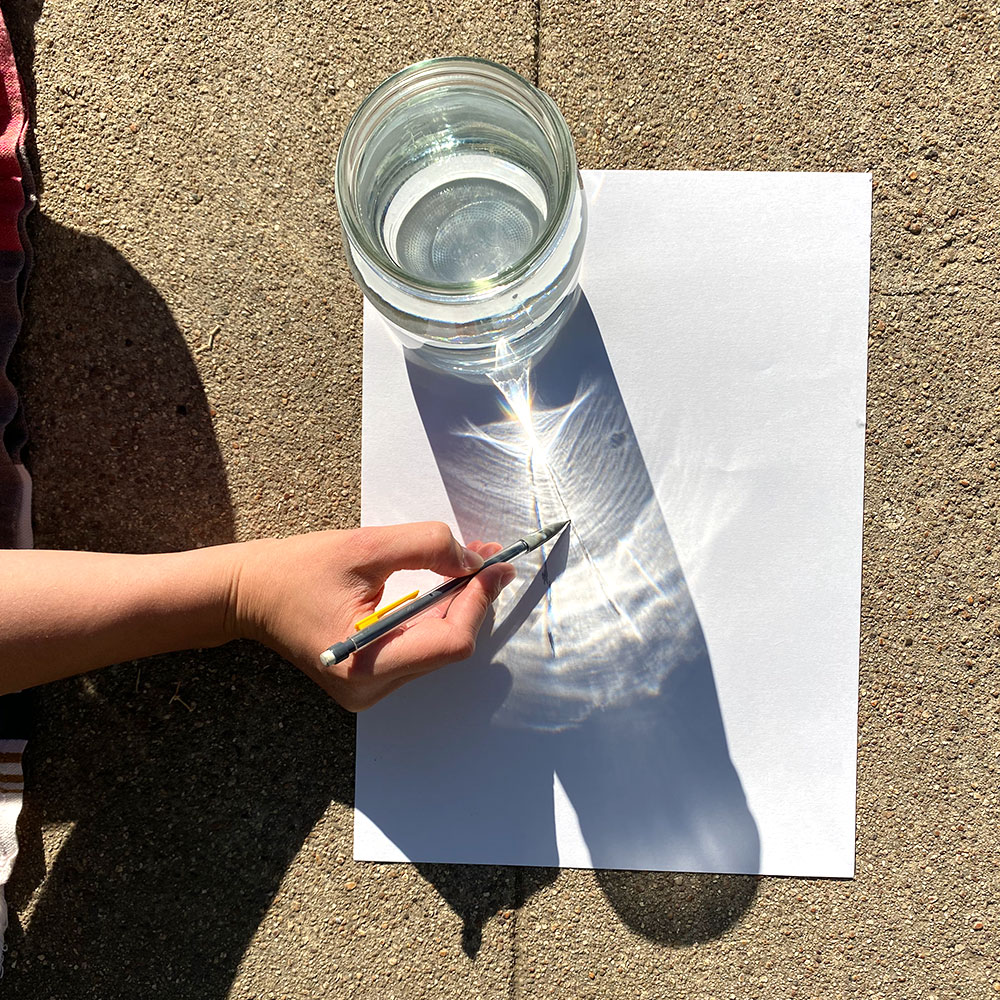 Using a pencil to sketch the shapes created by the light and shadows of the sun shining through the water filled glass.