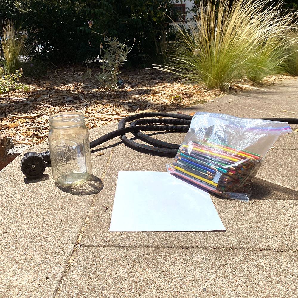Empty glass, white paper, bag of colored pencils and garden hose arranged on sidewalk in the sun.