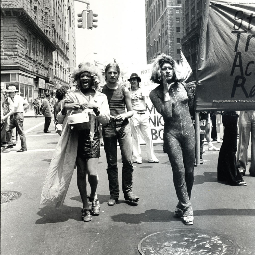 Black and white photo of three people marching in a protest.
