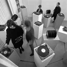 "Exhibit-goers mill among turntables and speakers during John Cage's ""33 1/3,"" an immersive sound art installation piece, in 1969 at the University of California, Davis."