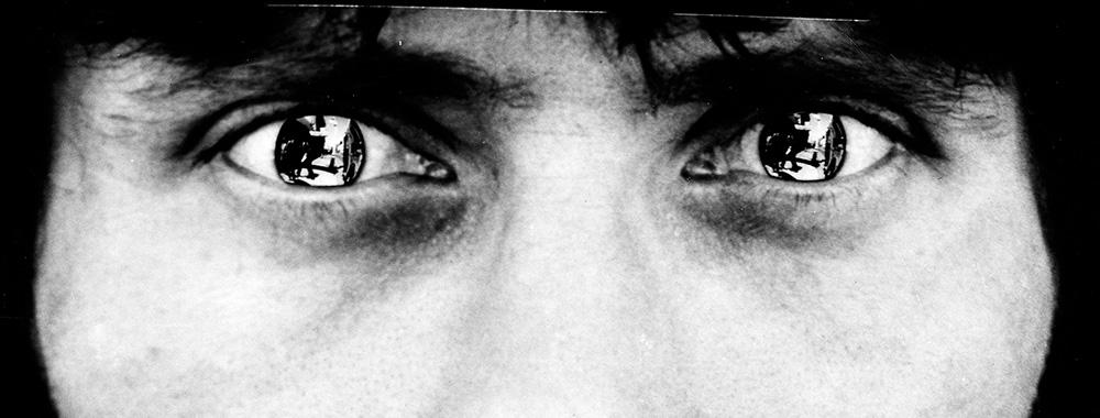 Black and white photo of man with reflective contacts in eyes.