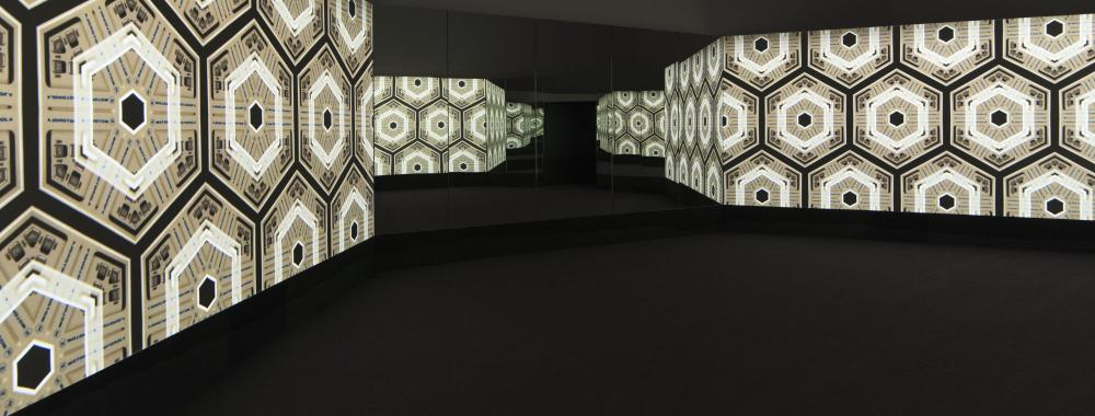 Hexagon pattern projected onto mirrors in dark room.