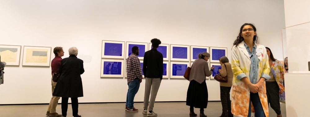 People viewing art in the museum gallery.