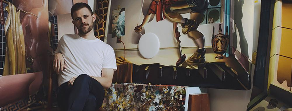 Artist Kyle Dunn sitting in art studio surrounded by paintings.