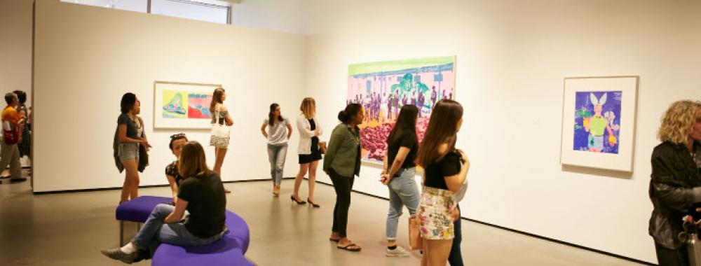 Photo of visitors in the gallery looking at art.